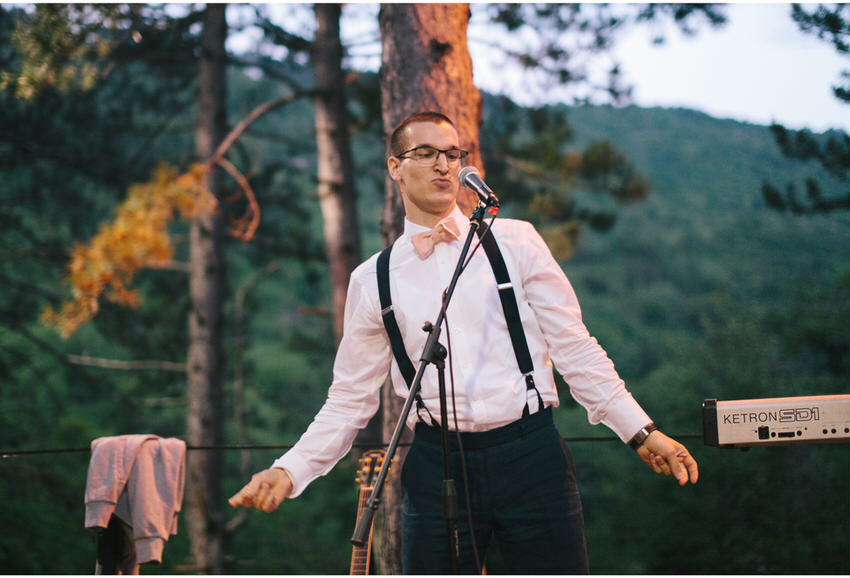 groom performin at a forest wedding