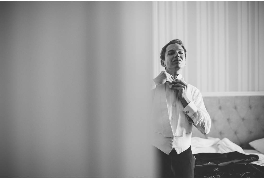 man tying bow tie in front of mirror
