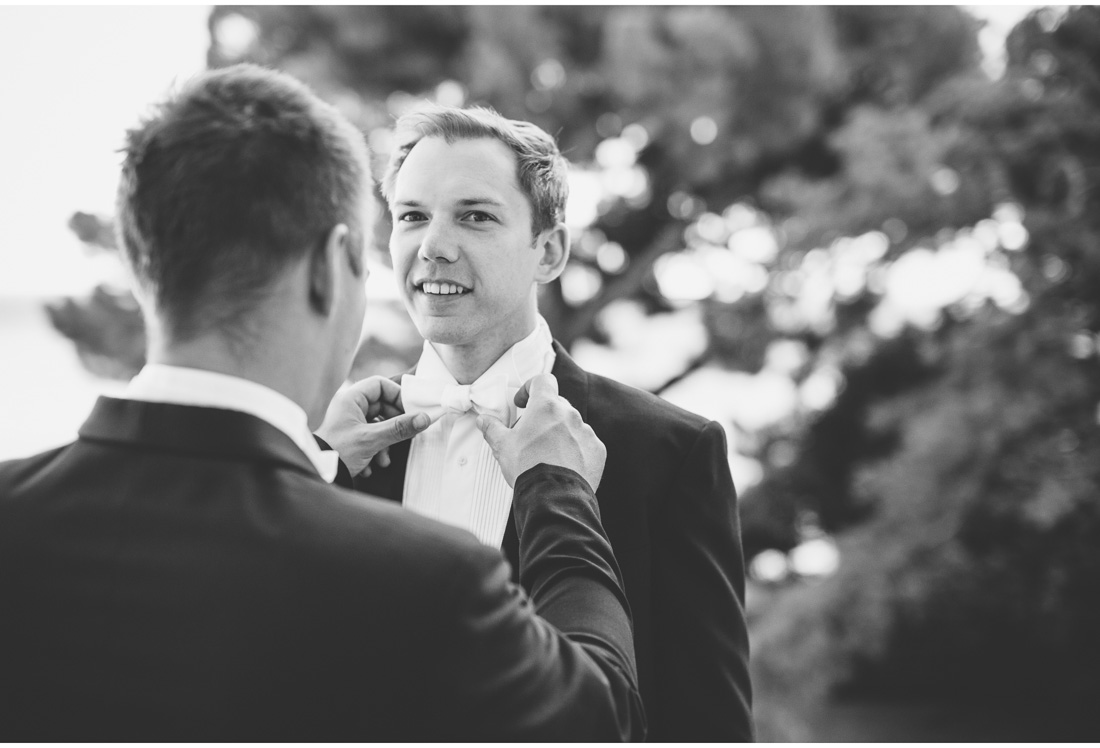 best man tying grooms bow tie