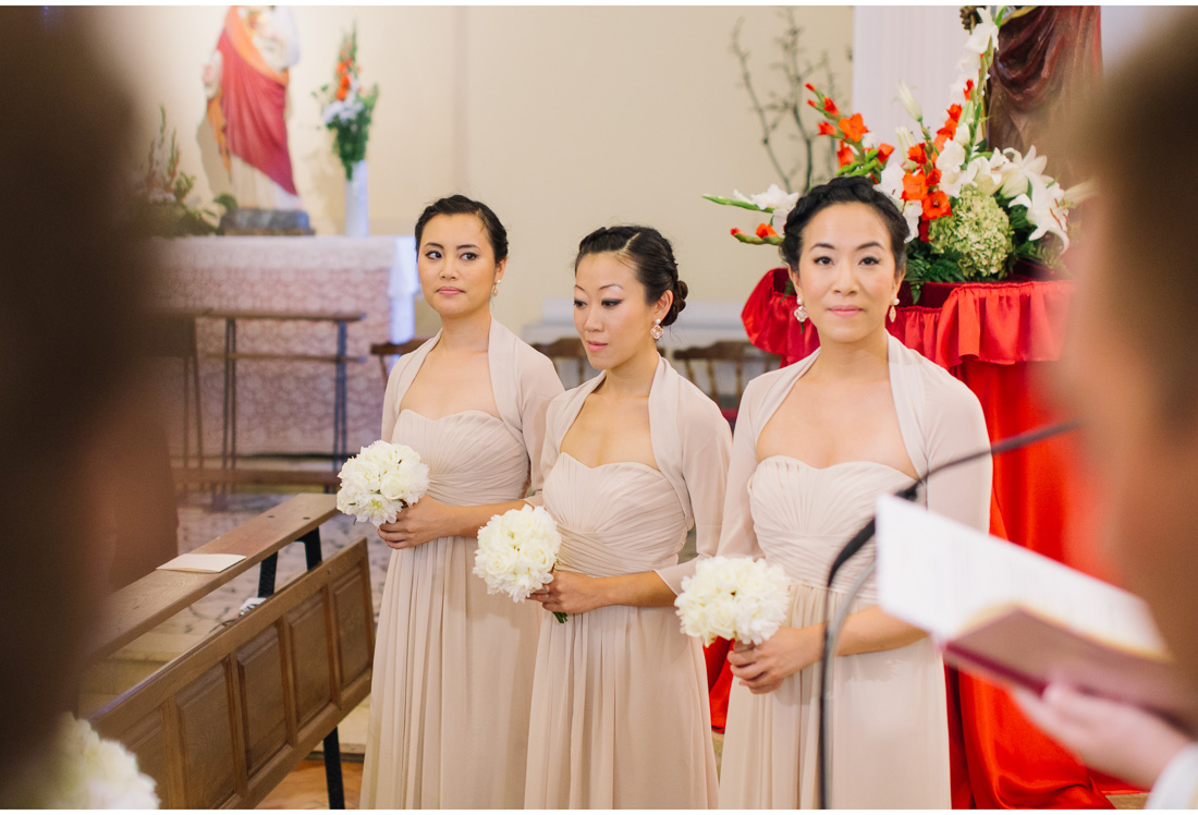 bridesmaids standing in church with flowers