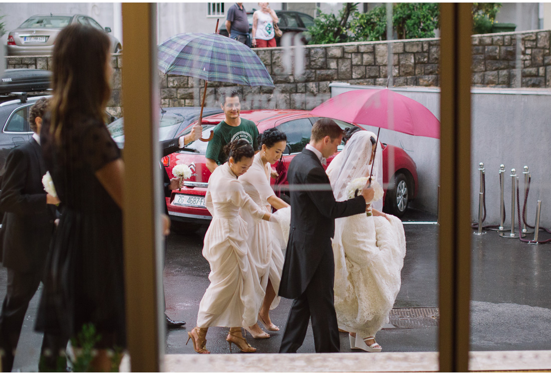 bride and groom entering a hotel in the rain