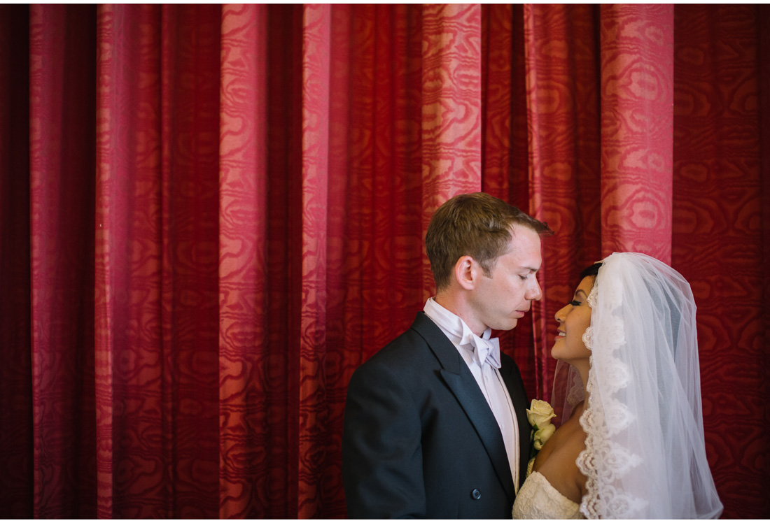 bride and groom pose in front of red background