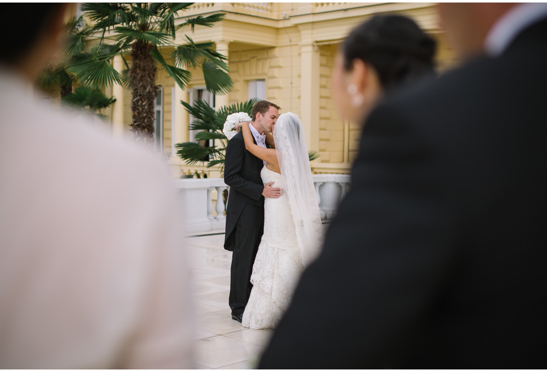 bride and groom kissing surrounded by people