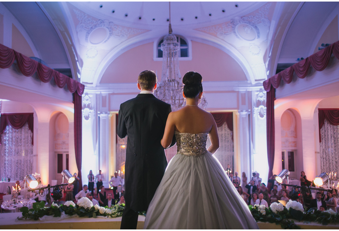 bride and groom stand on a balcony