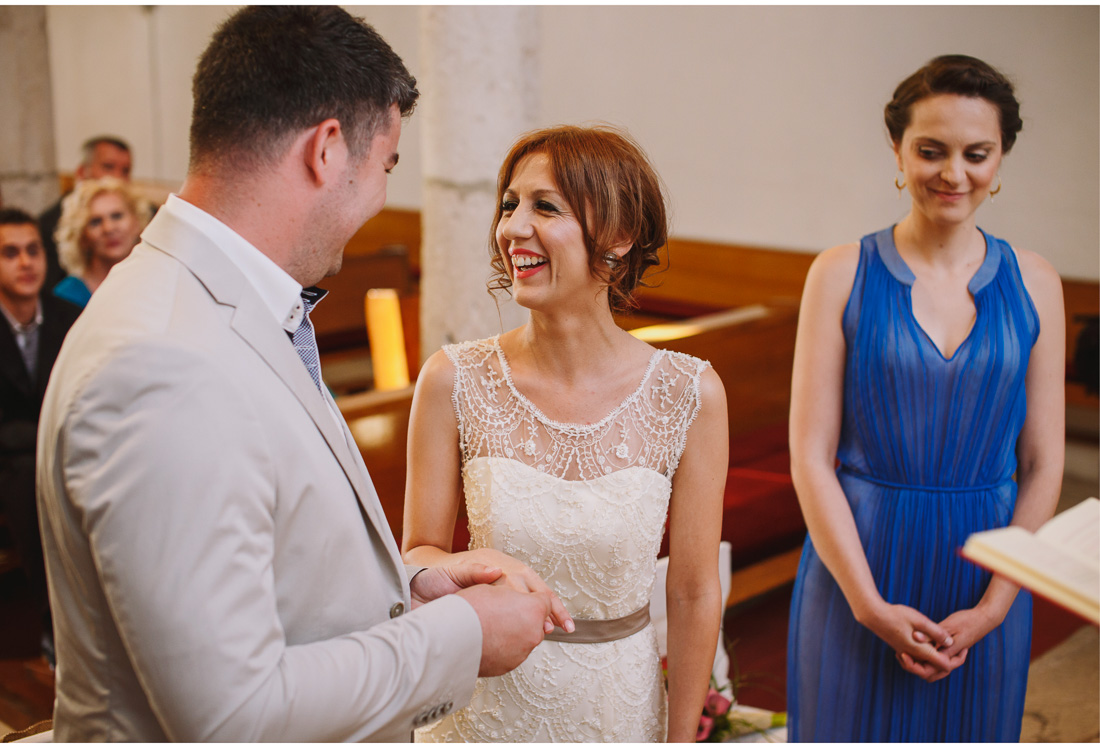 bride smiles as the groom puts a ring on her finger