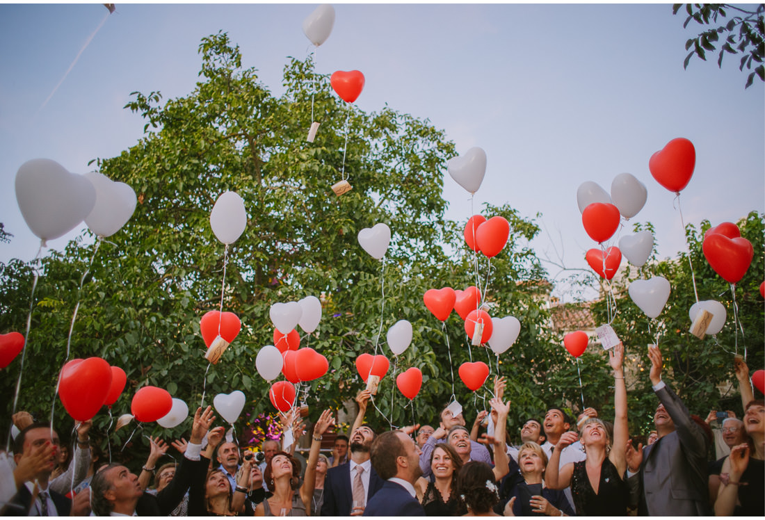 guests release balloons with messages for bride and groom