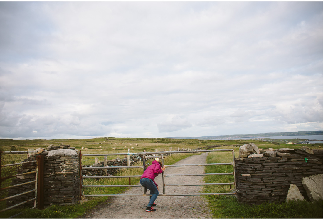 woman crossing the gate to a field in ireland