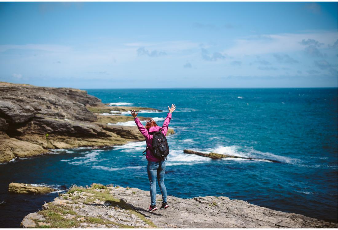 women jumps on ireland cliffs