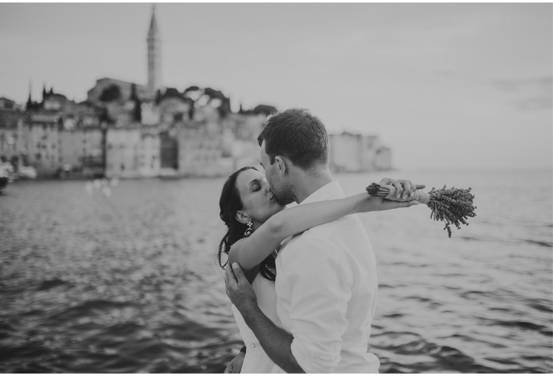 bride and groom kiss with rovinj old city in the background