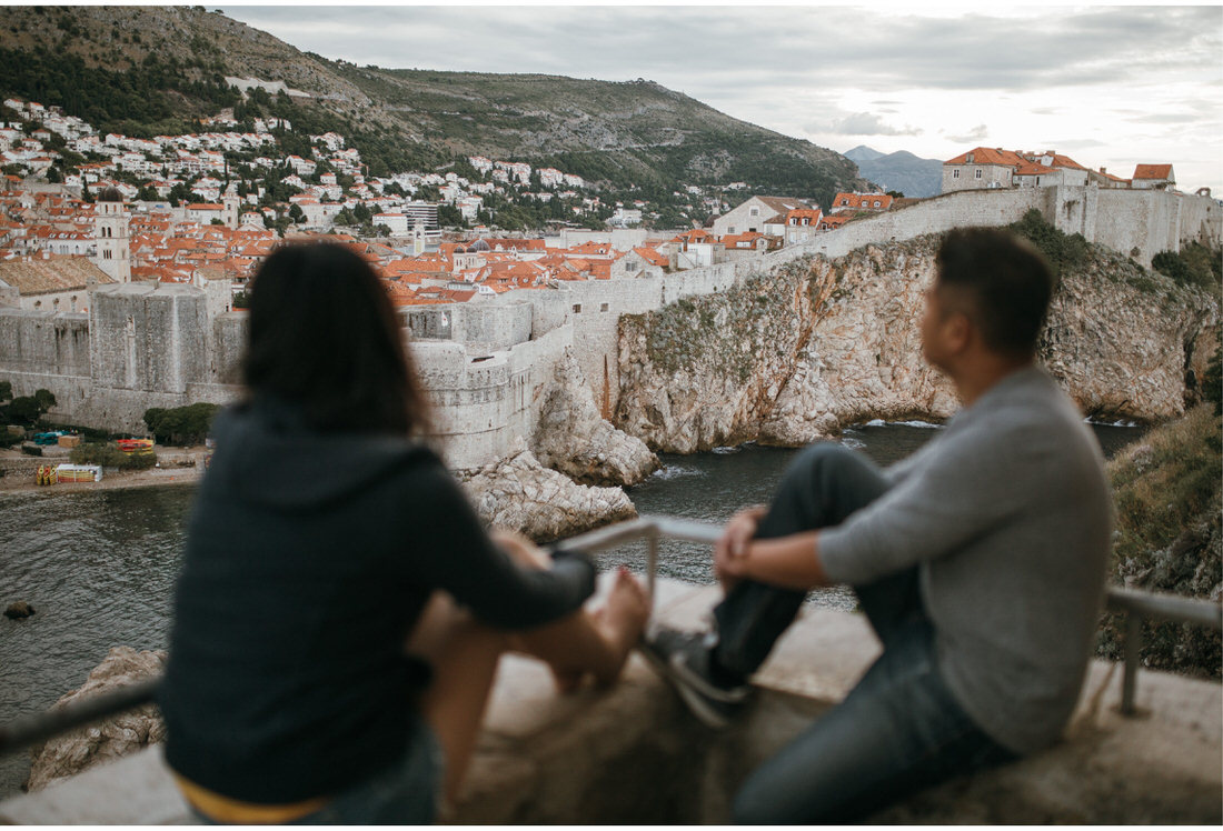 couple sitting on a wall in dubrovnik engagement photographer