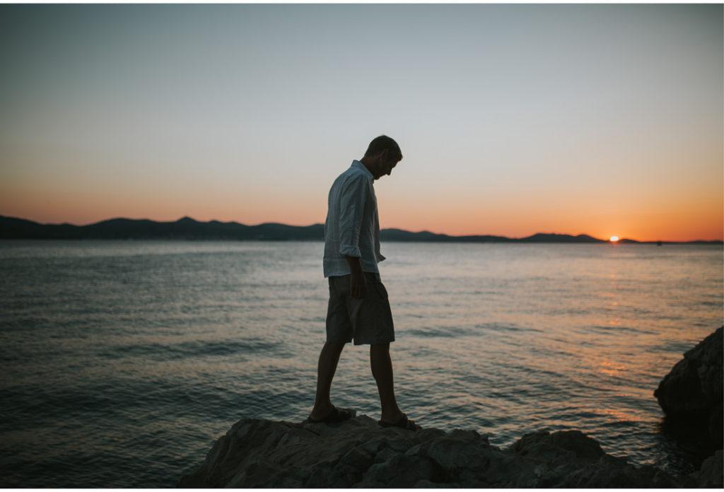man walking on rocks by the sea