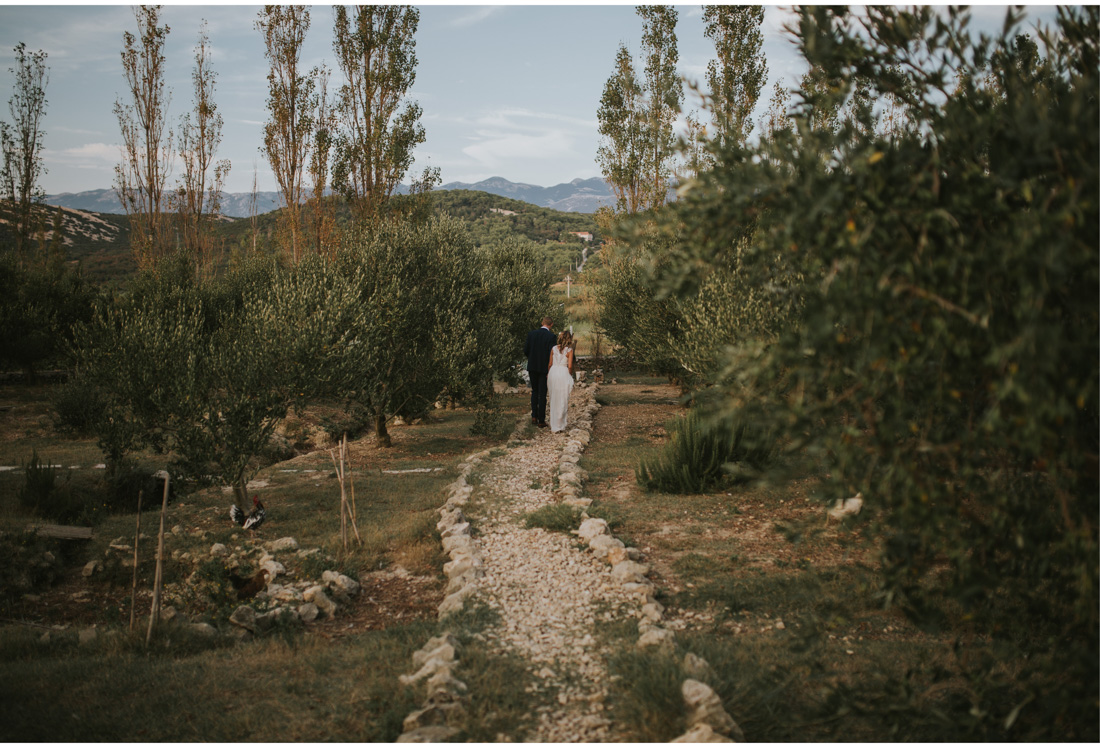 bride and groom walking through garden