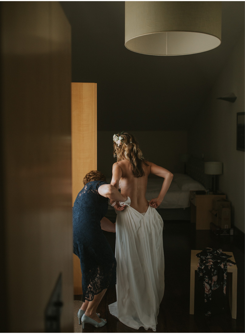 pretty bride putting on a wedding dress