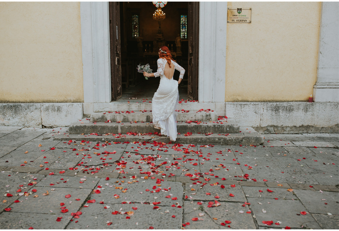bride in front of church floor covered with roses