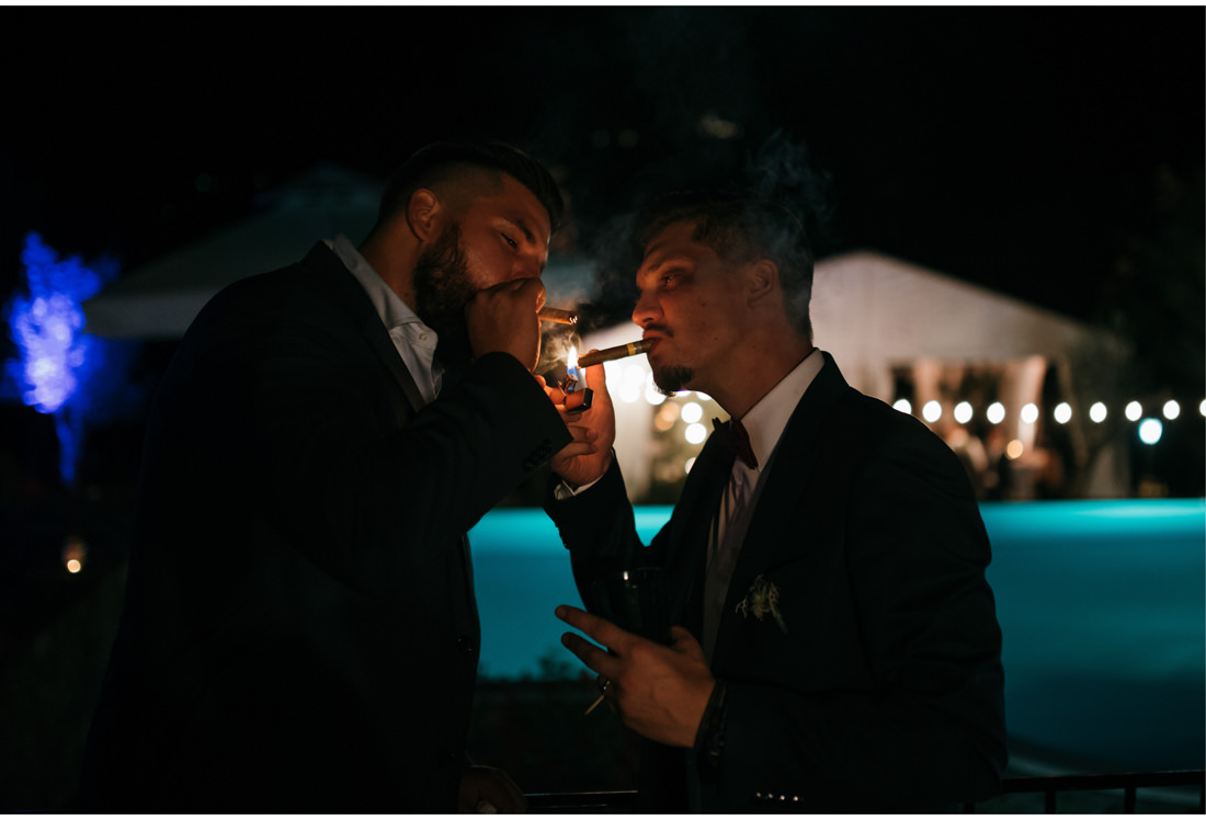 groom and best man smoke cigars