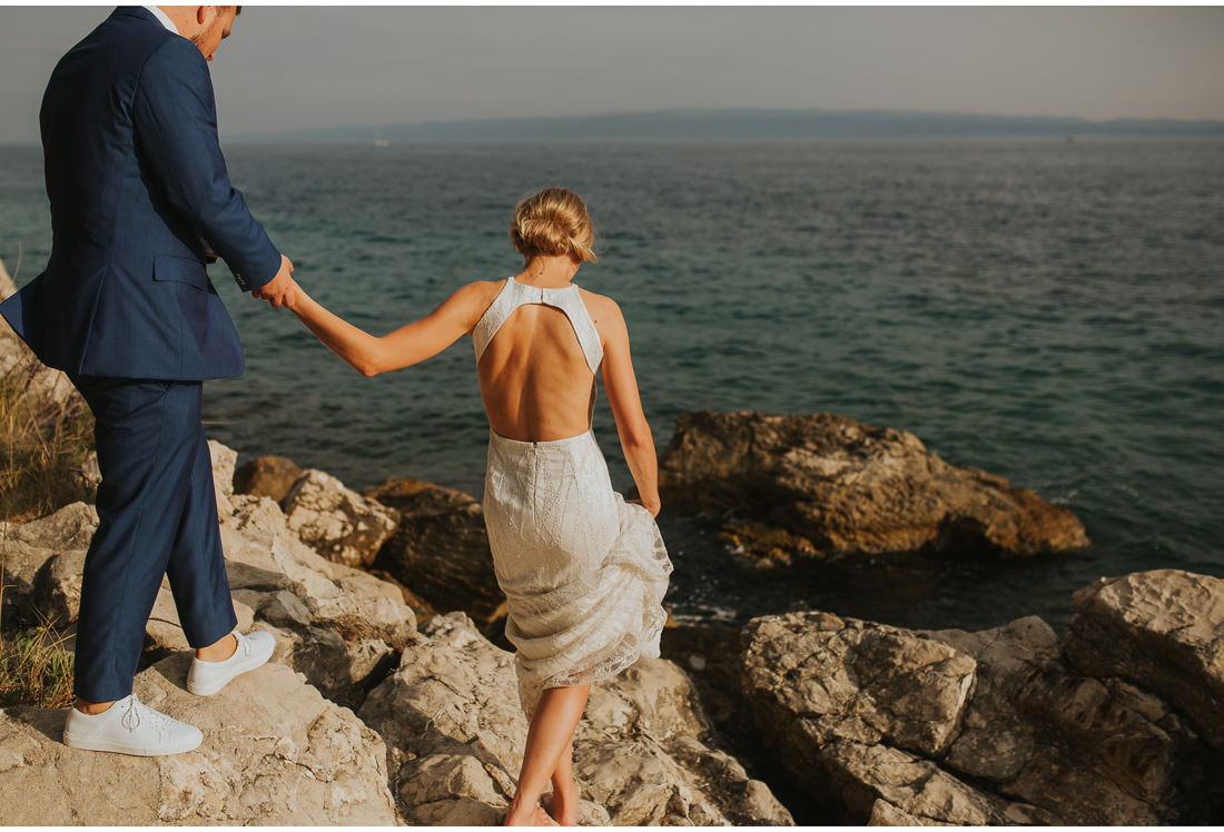 bride and groom walking on rocks by the sea