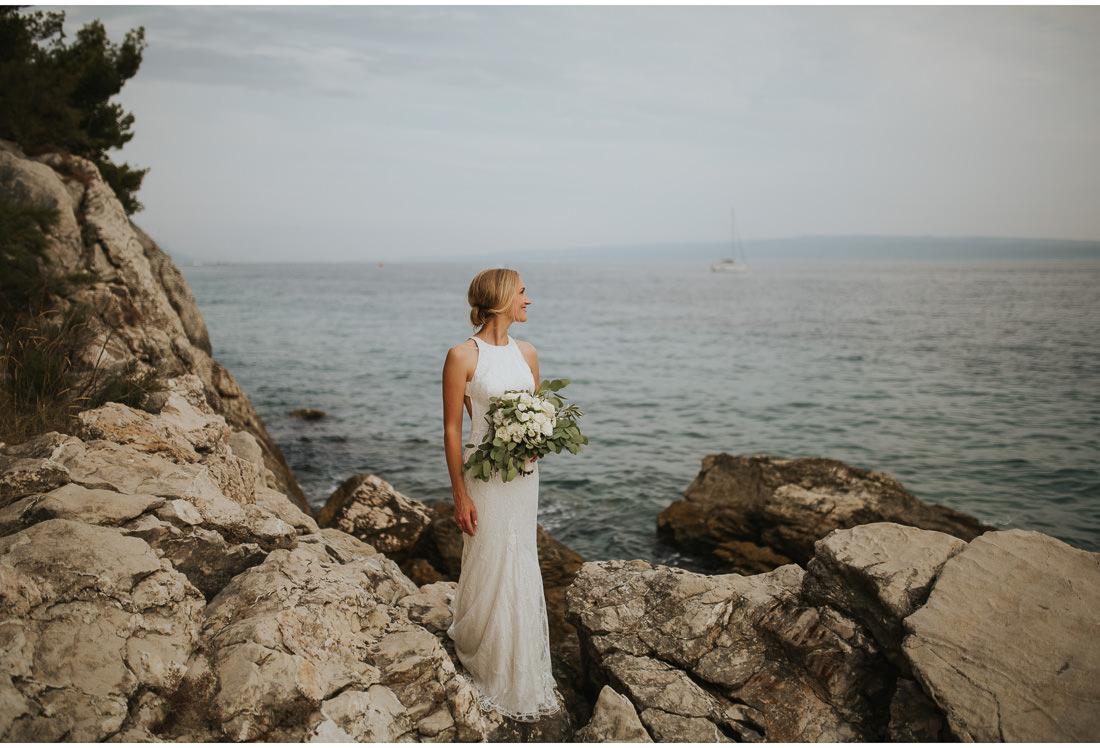 boho bride posing with flowers by the sea at villa dalmacija wedding