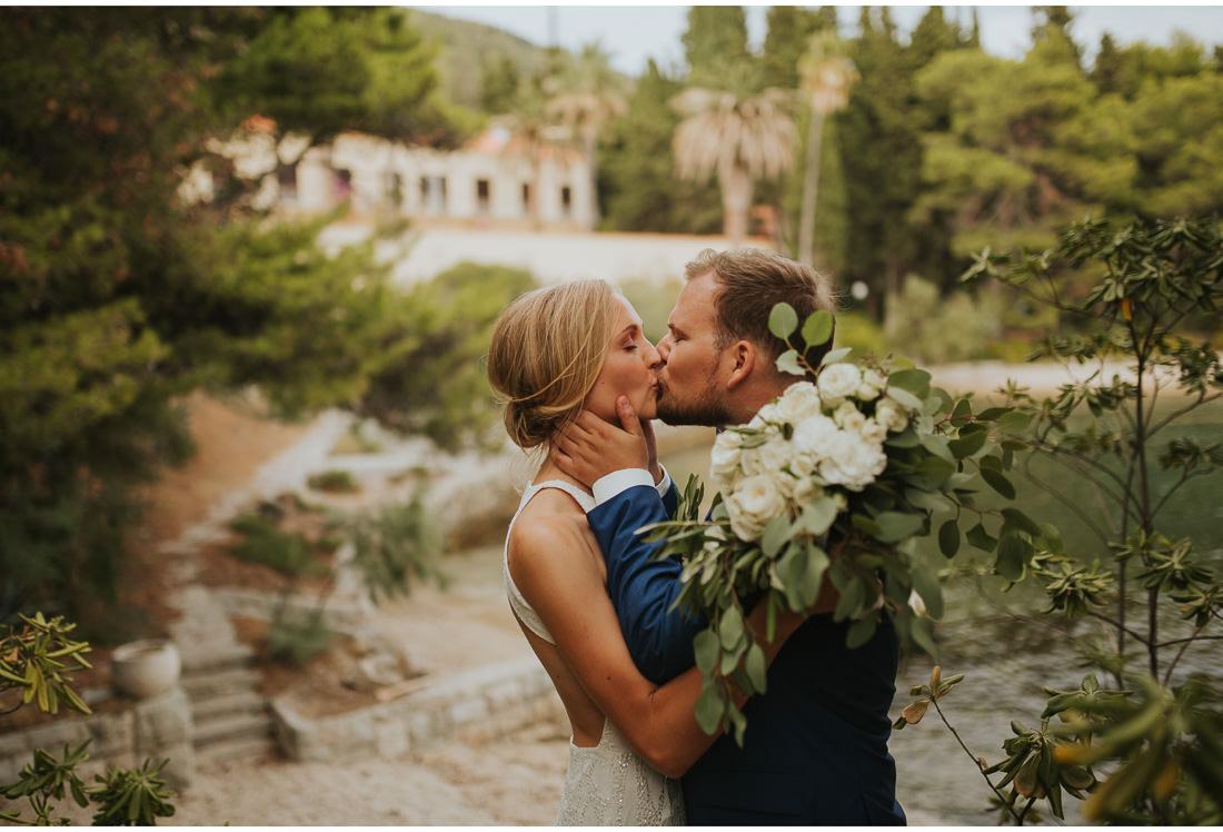 bride and groom kiss in front of villa dalmacija