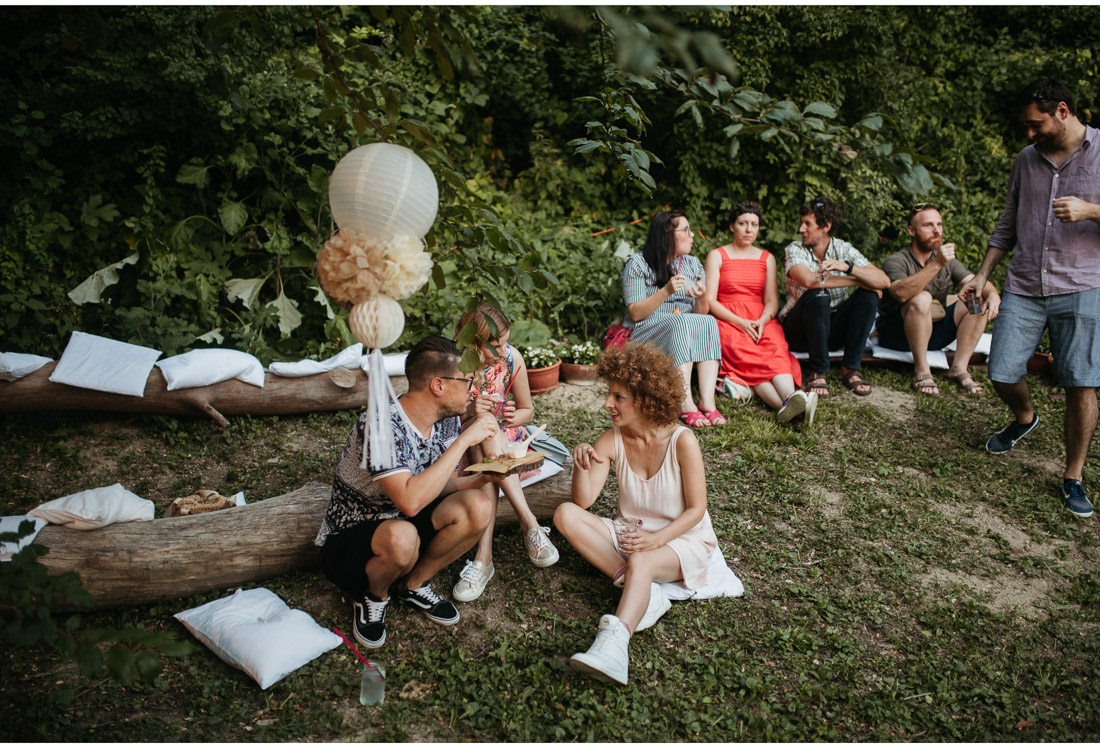 backyard wedding party guests sitting on grass