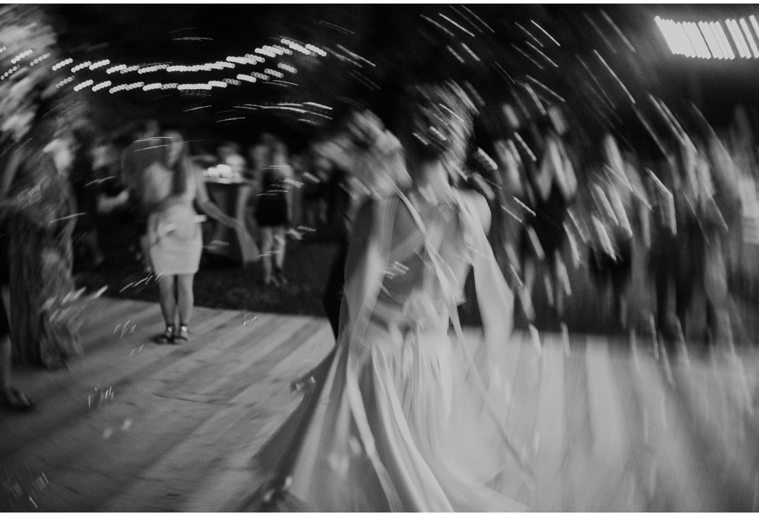 apstract image of a bride dancing at a backyard wedding party