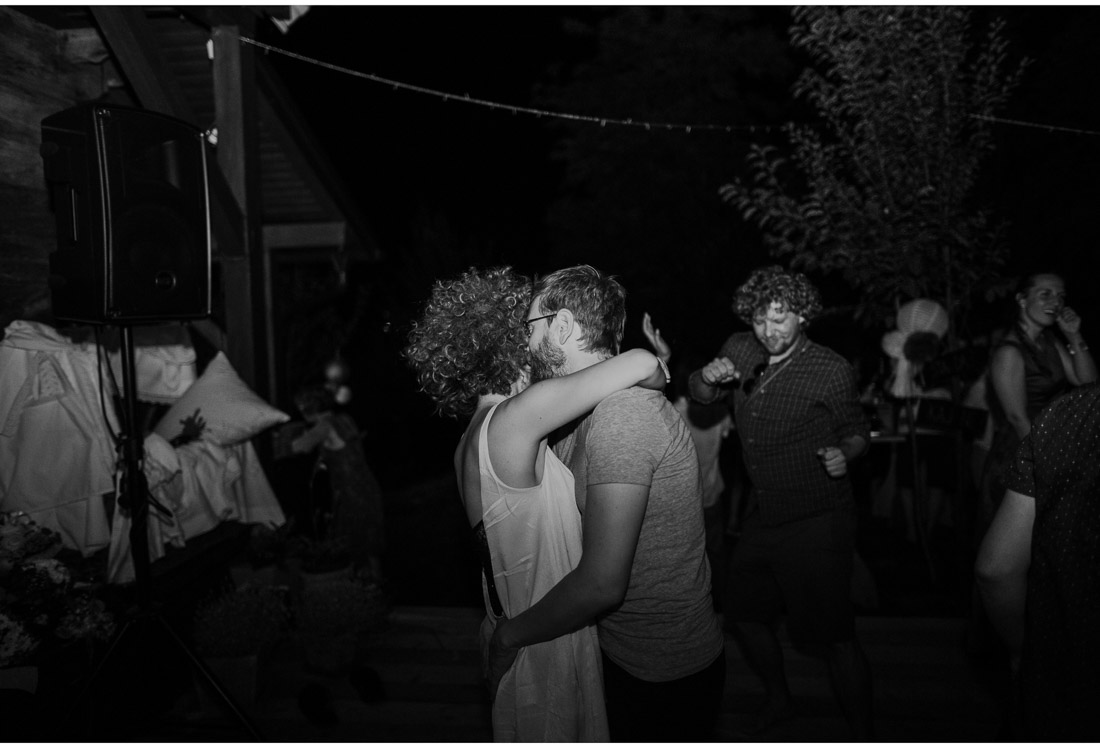 backyard wedding party guests dance and hug