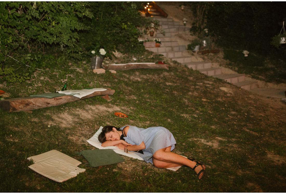 girl sleeping on the lawn at a backyard wedding