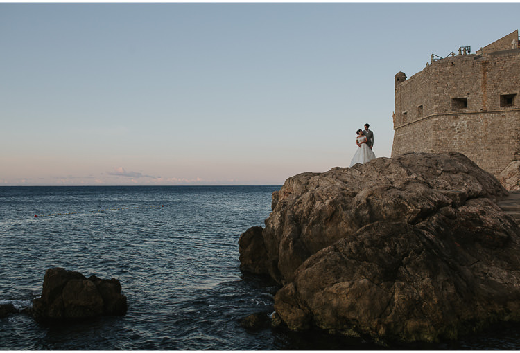 bride and groom pose at dubrovnik city walls