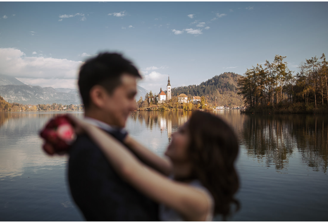 bride and groom out of focus on Lake Bled