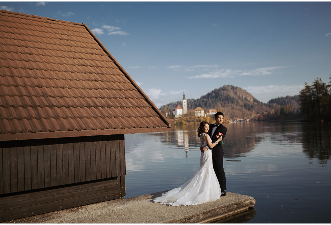 bride and groom posing on Lake Bled